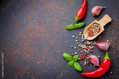 Plakat Widok z góry Wybór ziół przypraw. Czerwony pieprz, czosnek, liście bazylii, pieprz kukurydziany na ciemnym tle kamień betonowy stół. Koncepcja zdrowej żywności