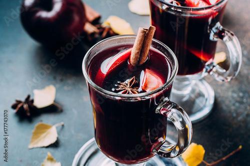 Plakat Grzane wino gorący napój spadek z owoców cytrusowych, jabłko i przyprawy w szkło na ciemnym tle betonu. Jesień gorący napój. Spadek liści jesienią
