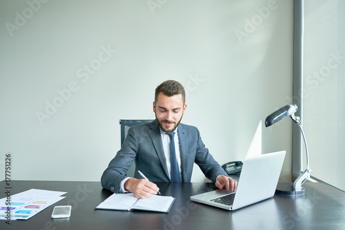 Fototapety, obrazy: Young bearded entrepreneur in classical suit taking notes while sitting at office desk and analyzing financial figures with help of laptop, waist-up portrait