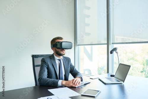Garden Poster Waist-up portrait of unrecognizable bearded entrepreneur wearing VR headset sitting at office desk wrapped up in work