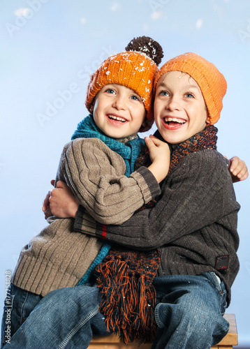 Valokuva  Small Series of two Bothers with orange hats in Winter Snow Background: Hapiness