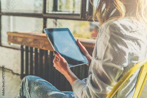 Obraz Sunny day. Close-up of tablet computer in hands of young woman sitting in room on chair.Hipster girl working online,blogging,chatting,checking email, watching video blog. Online marketing, education. - fototapety do salonu