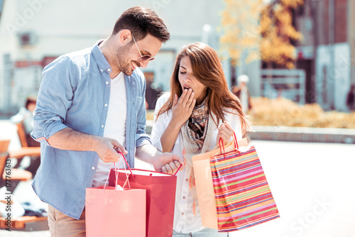 Fototapeta Uśmiechnięta atrakcyjna para z torba na zakupy w mieście.