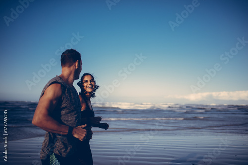 Fit couple running together on the beach
