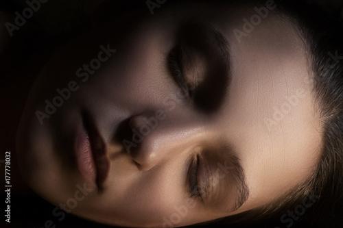 Plakat piękna kobieca twarz z zamkniętymi oczami w ciemności do spania