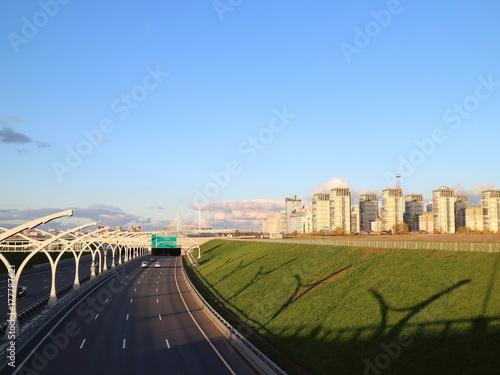 Plakat szybka droga o zachodzie słońca nad miastem morza