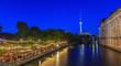 canvas print picture - Aufnahme eines Biergartens am Berliner Spreeufer gegenüber des Bode Museums Abends zur Dämmerung in der blauen Stunde mit Fernsehturm im Hintergrund und Lichtspiegelungen in der Spree