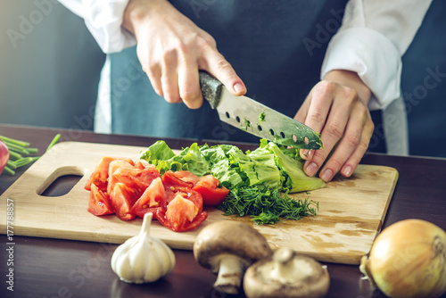Poster Cuisine The chef in black apron cuts vegetables. Concept of eco-friendly products for cooking