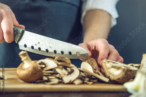 Plakat Szef kuchni w czarnym fartuchu przecina grzyby nożem. Koncepcja ekologicznych produktów do gotowania