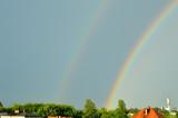 Fototapeta Tęcza - Tęcza na niebie po burzy nad dachami domów.