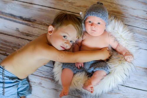 Fotografía  baby boy and his newborn brother on Woden Background