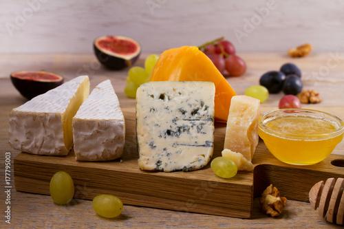 Plakat Płyta serowa. Różnorodni typ ser z winogronami, miodem, figami i dokrętkami na nieociosanym drewnianym stole, horyzontalnym