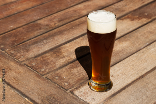 Photo  A craft beer (IPA) on a wooden table top.