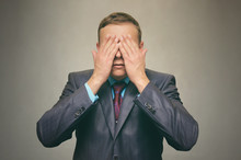 Young Man In Suit Closes His Eyes With His Hands. See No Evil.