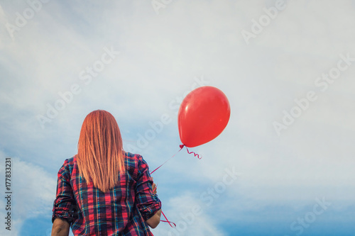 Photo  Redhead girl with red balloon against the sky.