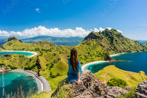 Foto Rear view of a young woman enjoying the awesome view of Padar Island, while sitt