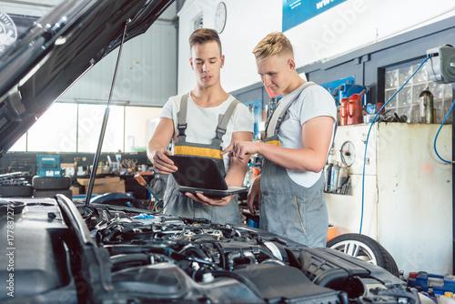 Plakat Doświadczony mechanik samochodowy używający laptopa do skanowania i interpretowania kodów błędów silnika obok praktykanta w nowoczesnym warsztacie samochodowym