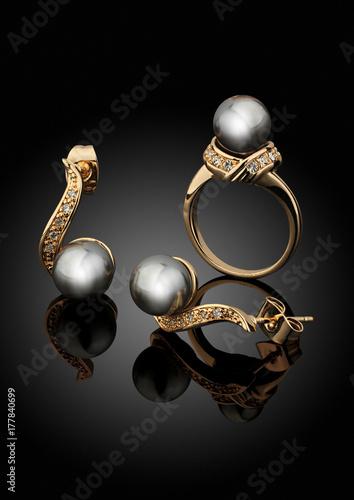 Zdjęcie XXL Złota biżuteria ustawiająca z perłami na czarnym tle z odbiciem