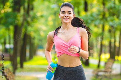 Fotografiet  The happy sportswoman running in the park