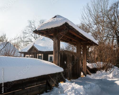 Plakat Słoneczny zimowy dzień w starej Rumuńskiej Homestead z drewnianą bramą ręcznie.