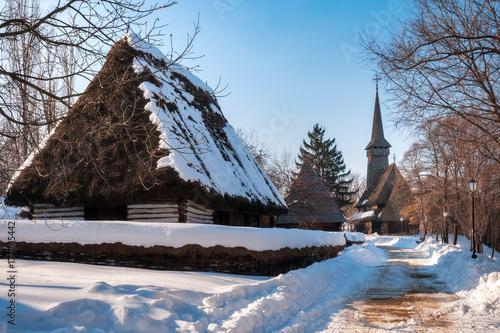 Zdjęcie XXL Pastoralny krajobraz z tradycyjną starą chałupą z pokrywającym strzechą dachem zakrywającym w śniegu i wysokim drewnianym kościół przy wioski muzeum w Bucharest, Rumunia.
