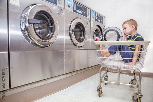 Fotografie, Obraz  Bored boy in the public laundry