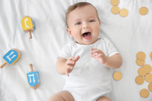 Cute Funny Baby Lying Near Dreidels And Chocolate Coins On Bed
