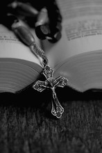 Rosary And Christian Bible Open On Table