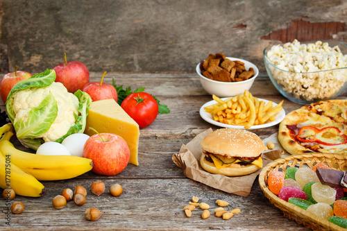 Fastfood and healthy food on old wooden background Poster