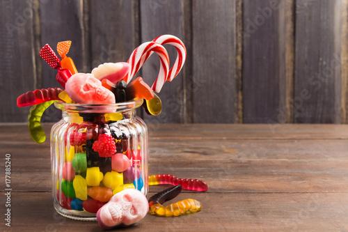 Zdjęcie XXL Różni kolorowi cukierki na szklanym słoju woth słodkich czaszkach, reat i dżdżownicach nad drewnianym tłem ,.