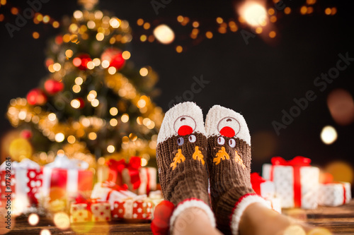 Foto op Canvas Kerstmis Detail of woman legs with knitted socks, Christmas tree with gifts on background