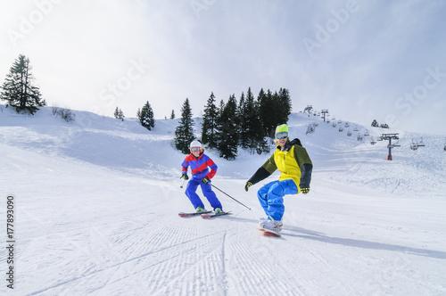 Foto op Aluminium Wintersporten Skifahrerin und Snowboarder gemeinsam auf der Piste unterwegs