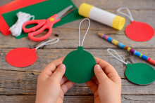 Child Made Red And Green Christmas Balls From Cardboard Paper. Child Holds Christmas Ball In His Hands. Step. Stationery On The Wooden Table. Easy Christmas Crafts For Kids To Make