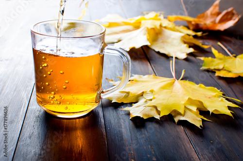 Zdjęcie XXL Filiżanka gorąca herbata w jesień dniu na ciemnego brązu drewnianym tle
