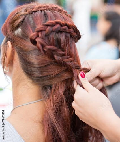 Plakat stylista splata kobiece warkocze na głowie