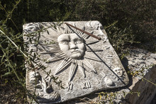 Old White Stone Sundial Clock With A Rusty Metal Rod As Clock Hand And Shadow In A Garden Bush