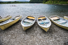 Rowing Boats With Paddles Docked On Lake Shore.