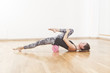 Leinwanddruck Bild - Beautiful woman pilates instructor stretching and warming up using foam roller