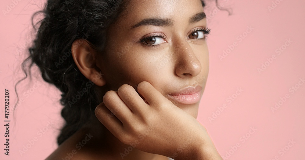Fototapeta Close up video of a happy and relaxed young woman with perfect olive skin fixing her wavy black hair isolated on white