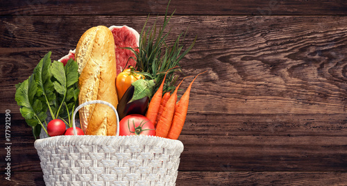 Fotografía  White basket full of groceries and vegetables on wood background 3D Rendering