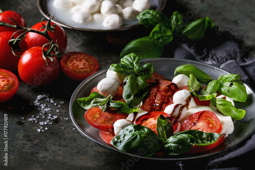 Fototapeta Italian caprese salad with sliced tomatoes, mozzarella cheese, basil, olive oil. Served in vintage metal plate with ingredients above over dark metal background. Close up. Rustic style obraz
