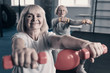 Elderly woman exercising with dumbbells in gym