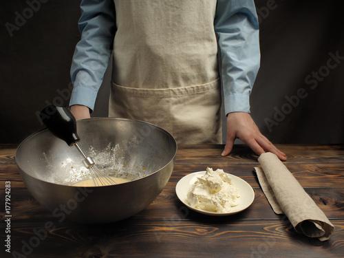"""Zdjęcie XXL Przepis gotowania tiramisu, część trzecia: """"Mieszanie masy jajka z mascarpone"""". Produkty na drewnianym stole: serek mascarpone, wstrząsana mieszanka żółtek jajecznych, trzepaczka do drutu."""