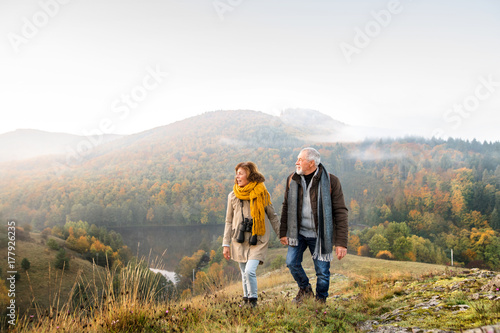 Cuadros en Lienzo  Senior couple on a walk in an autumn nature.
