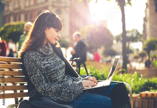 Woman using laptop outdoor sitting in the city street, urban scene - 177928810