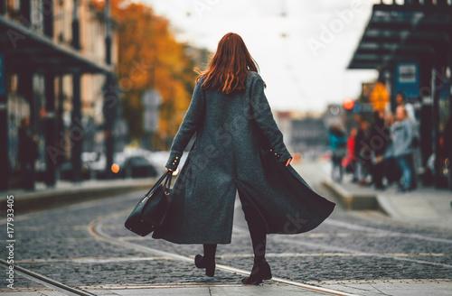 Fototapeta Trendy fashion woman in coat walking on the street, city scene