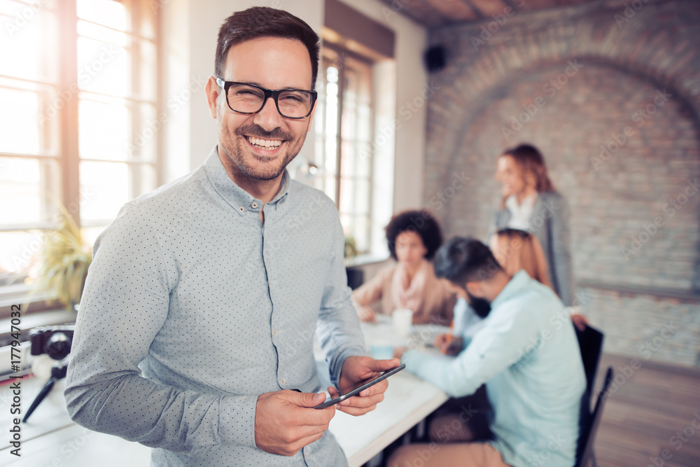 Fototapeta Portrait of smiling young man using tablet in office