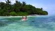 v08401 2 pretty young girls on a surfboard paddleboard with aerial view in warm blue sea water