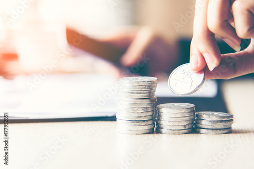 Fototapeta Businessman hand putting stack of coin money cover growing plant for the investment financial report.  Investment concept.. obraz