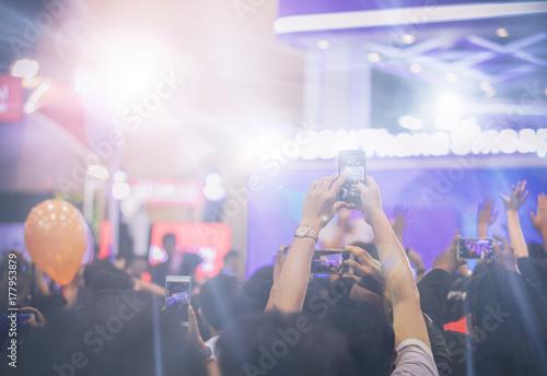 Plakat Azjatyckie kobiety trzyma mądrze telefon i stuka ekran dla brać obrazki na tłumie przy koncert sceną zaświecają, rozmyty tło